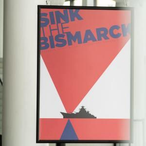 Plakat filmowy Sink The Bismarck. Czerwone, białe i niebieskie trójkąty, czarny okręt. Za plakatem widoczne słynne białe filary Oskardu i schody wiodące do sali widowiskowej.