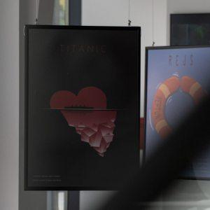 Plakat filmu Titanic - na tle czerwonego serca łączącego się z górą lodową czarny zarys statku. Obok plakat filmu Rejs - koło ratunkowe.