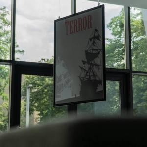 Robione zza kanapy zdjęcie plakatu filmowego Terror, a na nim - czarny i biały żaglowiec. Za szklaną fasadą CKiS widoczna zieleń drzew.
