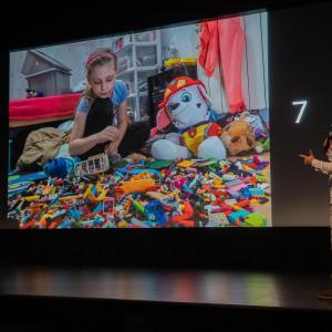 Po prawo Tomasz Kulas mówi do mikrofonu. Omawia zdjęcie numer 7, na którym jest siedząca na podłodze dziewczynka. Obok niej zabawki i sterta klocków.