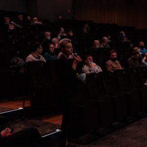 Justyna Kałużyńska-Markocka mówi do mikrofonu. Za nią siedzący w fotelach uczestnicy FotoBitwy.
