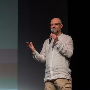Tomasz Kulas w lewej ręce trzyma mikrofon, lewą ma uniesioną.