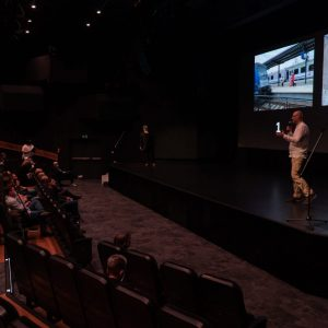 Marek Lapis i Tomasz Kulas stoją na scenie. Przed nimi cztery rzędy foteli z siedzącymi widzami. Na ekranie wyświetlone zdjęcia z numerami 1 i 4.