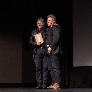 Na scenie trzymający nagrodę Franciszek Kupczyk i Marek Lapis. Franciszek Kupczyk opiera lewą dłoń na ramieniu jurora. Na głowę ma założoną chustkę, związaną na karku.