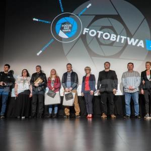 Zdjęcie grupowe na scenie jurorów, organizatorów i nagrodzonych. W tle logo FotoBitwa.