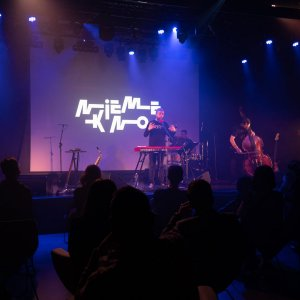 Sala klubowa Oskardu. Siedzące tyłem ciemne sylwetki publiczności. Na scenie zespół. W tle wyświetlony napis Nieme Kino.
