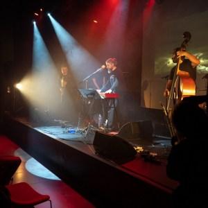 Zespół na scenie. Trzy sylwetki fotografujących.