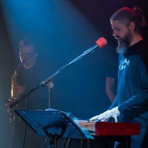 Pośrodku stojący przy czerwonym mikrofonie klawiszowiec. Ubrany w czarna bluzę z napisem Nieme Kino. Ma brodę i włosy związane w kitkę. Za nim saksofonista.
