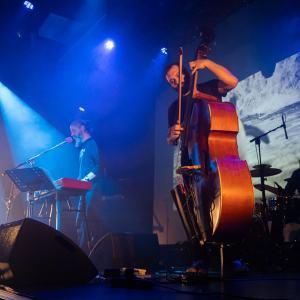 Zdjęcie zrobione z dołu. Na pierwszym planie oświetlony kontrabasista, za nim klawiszowiec, w tle ciemna postać perkusisty.