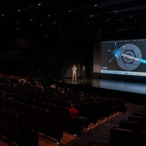 Zdjęcie z góry. Rzędy foteli i siedzący w nich uczestnicy. Na scenie jurorzy i wyświetlone logo festiwalu.