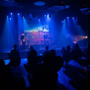 Niebieska poświata. Plecy publiczności i zespół na scenie. W tle zdjęcie z palmami.