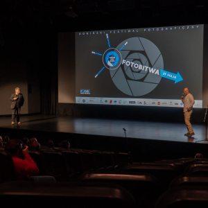 Na przeciwległych krańcach sceny stoją Marek Lapis i Tomasz Kulas. Na ekranie wyświetlone logo Konińskiego Festiwalu Fotograficznego.