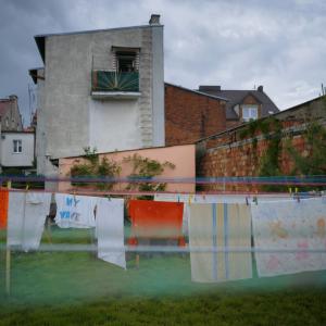 Na piewrszym planie suszące się na sznurach pranie. Po prawo ściana z cegieł. W tle czerwony samochód i kamienice (zdjęcie nr 6).