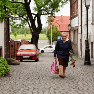 Idąca ulicą Śliską w Koninie starsza kobieta. W prawej ręce trzyma torby, w lewej - czerwoną różę. W tle dwa auta: czerwone i białe.(zdjęcie nr 12)