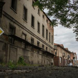 """Popadająca w riunę kamienica Stefanii Esse w Koninie. Po lewo pionowy znak drogowy """"droga z pierwszeństwem przejazdu"""". W tle kamienice Starówki.(zdjęcie nr 15)"""