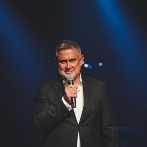 Marcin Kydryński ubrany w białą koszulę i ciemną marynarkę, w prawej dłoni trzyma mikrofon. W tle mroki sceny i dwa łagodne snopy światła.