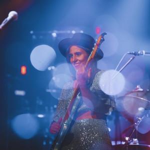 Uśmiechnięta Kinga Głyk gra na gitarze. Za nią i przed nią statywy z mikrofonami. W tle perkusja.