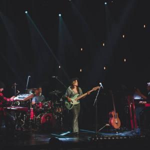 Kinga Głyk z zespołem - klawiszowcami i perkusistą. Ciemne tło z jasnymi punktami świateł.