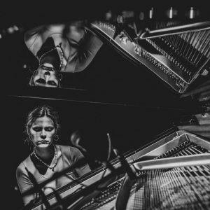 Pianistka Pola Atmańska i jej odbicie w uniesionym wieku fortepianu. Zdjęcie czarno-białe.