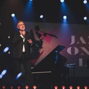 Marcin Kydryński na scenie. Za nim fortepian i wyświetlony na ekranie napis Jazzonalia