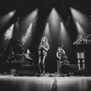 Na scenie Oskardu O.N.E Quintet, od lewej: pianistka Pola Atmaańska, saksofonistka Monika Mus, kontrabasistka Kamila Drabek, skrzypaczka Dominika Rusinowska. Nad nimi światła reflektorów. Zdjęcie czarno-białe.