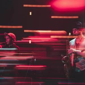 Jakub Kurek i Olaf Węgier. Zdjęcie utrzmane w czerwonej tonacji z efektem malowania światłem.