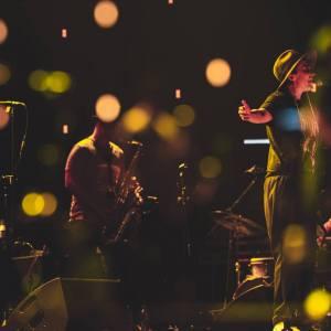 Paulina Przybysz przy mikrofonie. Ma rozłożone w bok ręce, na głowie kapelusz. Za nią muzycy z EABS. Zdjęcie z plamami światła.