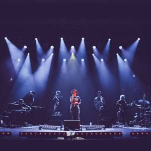 Paulina Przybysz i komplet EABS na scenie. Postać wokalistki jest barwna, stojacy za nią muzycy w ciemnej tonacji. W tle światłą reflektorów.