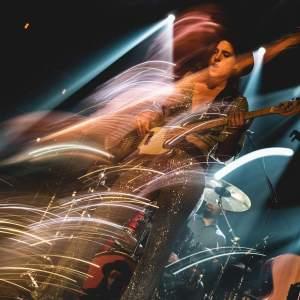 Zdjęcie z efektem malowania światłem. Kinga Głyk w ciemnym kapeluszu i kostiumie ze srebrnych cekinów gra na gitarze. W tle perkusja. Po prawo oparta gitara.