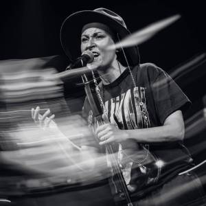 Nałożenie zdjęć. Paulina Przybysz w kapeluszu, śpiewa do mikrofonu, lewą dłonią ściska statyw, prawą unosi nieznacznie w górę. Zdjęcie czarno-białe.