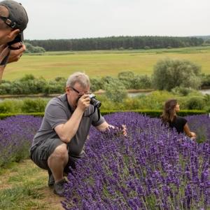 Po lewej odwrócony tyłem mężczyzna w żółtych spodenkach i białej koszulce trzyma aparat przy twarzy. Pośrodku kucający mężczyzna z aparatem przy twarzy. Lewą dłonią rozchyla łodygi lawendy.  Po prawej w tle kucająca bokiem kobieta patrzy w górę.