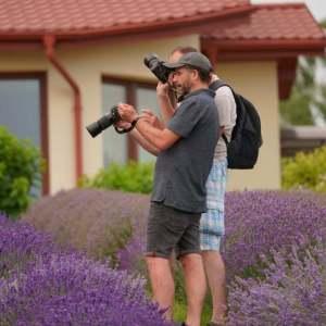 Dwóch fotografów trzyma aparaty. Na wyświetlaczu oglądają prace jednego z nich. Wokół nich krzewy lawendy. W tle fragment budynku.
