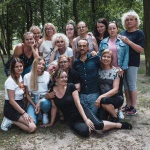 Zdjęcie grupowe uczestników warsztatów. Plener, polanka wśród drzew.