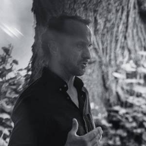 Prowadzący warsztaty Marek Kościółek. Stoi bokiem, za nim drzewo i budynek. Zdjęcie czarno-białe.