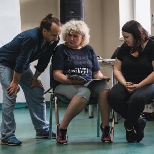 Po lewo Marek Kościółek stoi na rozstawionych nogach, ręce opiera na kolanach. Dwie kobiety siedzą obok niego na krzesłach (jedna z nich to Lucyna Lenard-Woźniak). W tle stolik z laptopem, okno i flipchart.