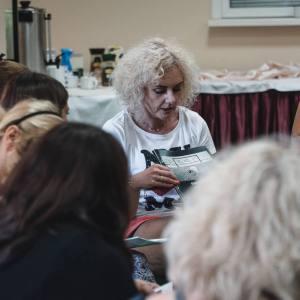 Widziane od tyłu głowy uczestniczek warsztatów. Paulna Pachulska-Wojdak trzyma magazyn i mówi. Po prawo kobieta z dobieranymi warkoczami, tatuażem i czarnej koszulce w białe wzorki. W tle bufet kawowy.