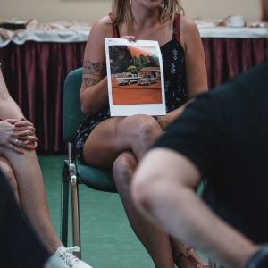 Siedząca na krześle kobieta z tatuażem prezentuje reprodukcję, na której widać dwa samochody. Po lewo noga innej uczestniczki, po prawo łokieć i rękaw czarnej koszulki.