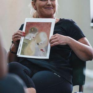 Uśmiechnięta blondynka siedzi na krześle. Przed sobą trzyma reprodukcję obrazu.