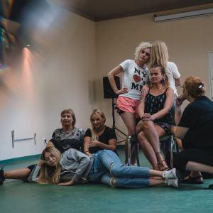 Scenka z warsztatów. Jednak kobieta leży, jedna kuca, dwie siedzą na podłodze, jedna na krześle. Obok niej stoi Paulina Pachulska-Wojdak, opierając się o odwróconą tyłem blondynkę.  W lewym górnym roku odbicie nóg z efektem rozszczepienia światła.