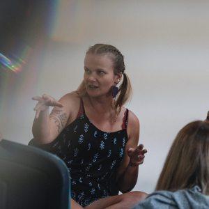 Kobieta z tatuażem gestykulje. Przysłuchują się trzy inne uczestniczki. W lewym górnym rogu efekt rozszczepienia światła.