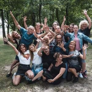 Zdjęcie grupowe uczestników warsztatów, machających do fotografa. Polanka pośród drzew.