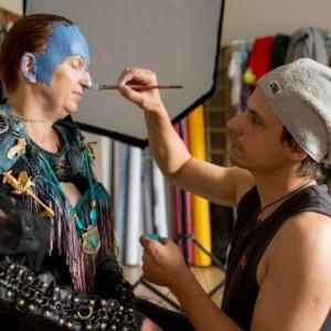 Marcin Urzędowski podczas malowania makijażu rudowłosej kobiecie. Ubrana jest ona w  strój wojowniczki.
