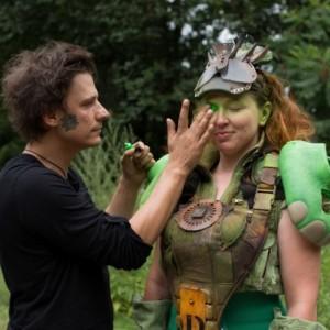 Marcin Urzędowski charakteryzuje rudowłosą kobietę w zielono-brązowym stroju inspirowanym marvelowskimi bohaterami.