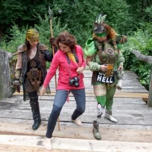 Madame Miko pokazuje dwóm przebranym kobietom, w jaki sposób mają pozować. Wszystkie mają wyciągniętą prawą nogę do przodu na długość jednego kroku.