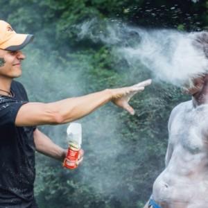 Marcin Urzędowski sypie biały proszek na ciało pozującego mężczyzny. Uczestnik pozbawiony jest lewej ręki na wysokości ramienia.
