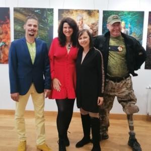Marcin Urzędowski i Madame Miko wraz z młodą kobietą w czarnej sukience oraz mężczyzną w zielonej czapce z daszkiem. W tle zdjęcia wykonane w ramach projektu Amputation.