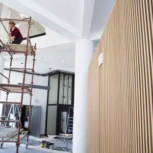 Hol. Po prawej stronie zdjęcia znajdują się drewniane płyty, z których zbudowano boks kasowo-szatniowy. Po lewej widać rusztowanie. Dwie kobiety polerują szybę - element poręczy schodów.