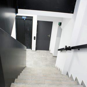 Klatka schodowa. Widok ze szczytu schodów na windę i drzwi.