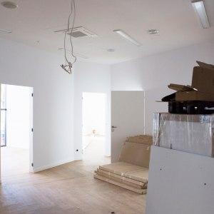 Jedno z pomieszczeń biurowych o białych ścianach i winylowej podłodze. Znajdują się w nim nierozpakowane kartony.