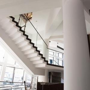 Widok spodu schodów, które prowadzą na poziom pierwszy budynku.